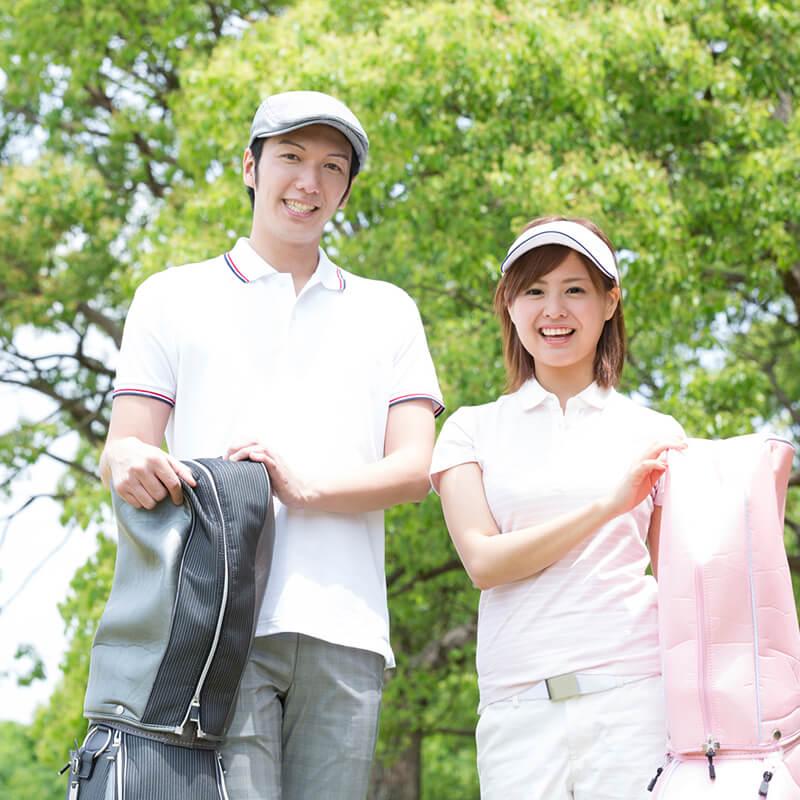画像:ゴルフクラブを抱えるカップル